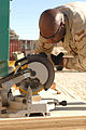 US Navy 061220-N-0193M-003 Boatswain's Mate 2nd Class Antoine Little lines the miter saw up with his pencil marks to ensure he cuts the board to the correct length.jpg