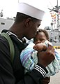 US Navy 070309-N-8544C-043 Seaman Brandon King Sr. embraces his five-month old son for the first time at the homecoming ceremony for guided missile frigate USS Taylor (FFG 50).jpg