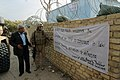 US Navy 071206-M-4746J-017 U.S. Marine Corps Lt. Col. Nathan I. Nastase attached to Personal Security Detail, 3rd Battalion, 3rd Marines reads a banner with an Iraqi police officer outside a police station.jpg