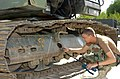 US Navy 080826-A-1497L-012 Constructionman 3rd Class Chance Keifer greases the tracks of a land excavator.jpg