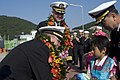 US Navy 081008-N-9123L-003 Lt. Cmdr. Robert Ogden, executive officer of the guided-missile destroyer USS John S. McCain (DDG 56), thanks a Korean child after receiving a traditional flower wreath presented to welcome McCain to.jpg