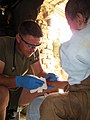 US Navy 090708-M-6159T-018 U.S. Navy Lt. Eric Shafer treats a local child with an infected foot in Helmand Province, Afghanistan.jpg