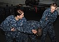 US Navy 100125-N-2798F-002 Master-at-Arms 1st Class Andria Sanders and Aviation Ordnanceman 3rd Class Patrick Yeger practice self-defense techniques on a fellow Sailor.jpg