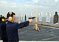 US Navy 100304-N-6676S-066 Chief Culinary Specialist Lawrence Messinea, from Chicago, fires a 9-mm pistol during a live-fire training exercise aboard the amphibious dock landing ship USS Gunston Hall (LSD 44).jpg