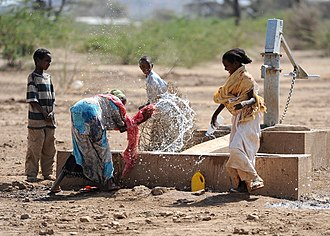 Water supply and sanitation in Ethiopia - Children play by a newly installed hand pump in the village of Jedane.