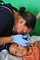 US Navy 110420-O-XX000-012 Aislinn Mangan, a registered nurse with Project Hope, tends to a patient during a Pacific Partnership 2011 medical commu.jpg