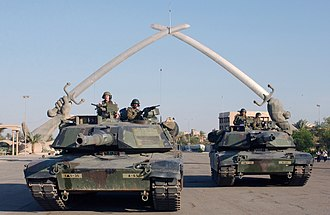 "2003 invasion of Iraq - U.S. Army M1A1 Abrams tanks and their crews of the 1st Armored Division pose for a photo in front of the ""Victory Arch"" monument at Baghdad's Ceremony Square in November 2003."