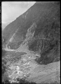 View of a steep hill, a stream at the bottom, with a railway line winding around, and evidence of a slip part way around the hill. ATLIB 294457.png