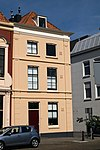 foto van Hoekpand met twee verdiepingen, schilddak en gepleisterde muren. Voorgevel met verdiepte lisenen en houten kroonlijst