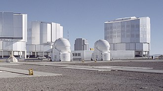 VLT Survey Telescope - The VST dome among VLT's telescopes. It is located in the background between two of the VLT auxiliary telescopes (small round enclosures).