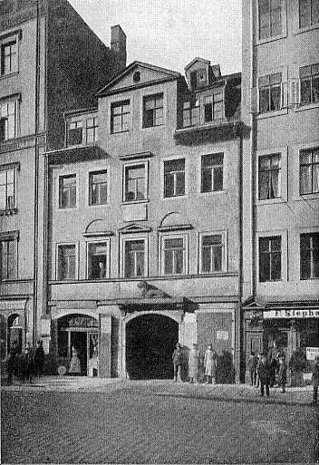 A building with four main storeys with an open shop to one side of an arched entrance and garret windows in the roof. A sculpted figure of an animal is above the arch.