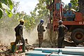 Water drilling technicians work together to drill for water in Djamde, Togo.jpg