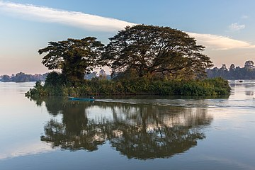 Water reflection of a green island at sunrise with blue sky and pirogue in Don Det Laos.jpg