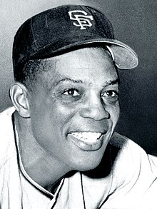 "A man wearing a baseball hat, which has an ""S"" and an ""F"" sewn onto it, smiles."