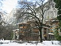 Photograph of The Ahwahnee in winter snow, amidst bare trees with the dramatic walls of Yosemite Valley rising behind.