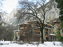A multi-story building with a wood and stone exterior is in the midground, a tree is in the foreground and high cliffs in the background. Snow is on the ground.