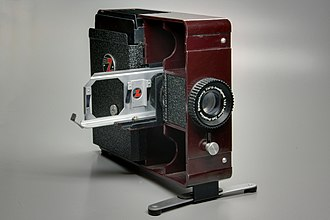 Reversal film - Slide projector, showing the lens and a typical double slide carrier