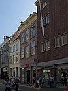 foto van Pand met geverfde lijstgevel, licht getoogde strekken, hardstenen raamdorpels, hijsbalk en jongere winkelpui
