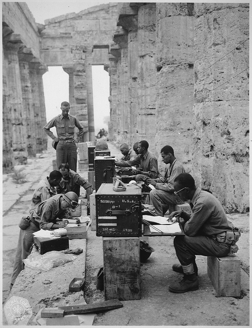 """A company of men has set up its office between the columns (Doric) of an ancient Greek temple of Neptune, built about 7 - NARA - 531170"
