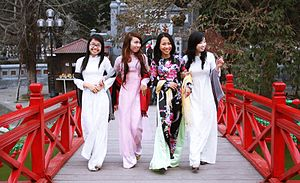 Culture of Vietnam - Young women wear áo dài at Hoan Kiem Lake.