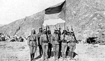 Soldiers of the Hashemite-led Arab Army holding the flag of the Great Arab Revolt in 1916. 030Arab (cropped).jpg