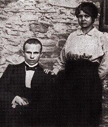Foto av en mann i dress som sitter og en kvinne som står ved siden av ham med hånden på skulderen