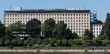 Landscape photograph of the 1955 German Foreign Office building, with trees in the foreground