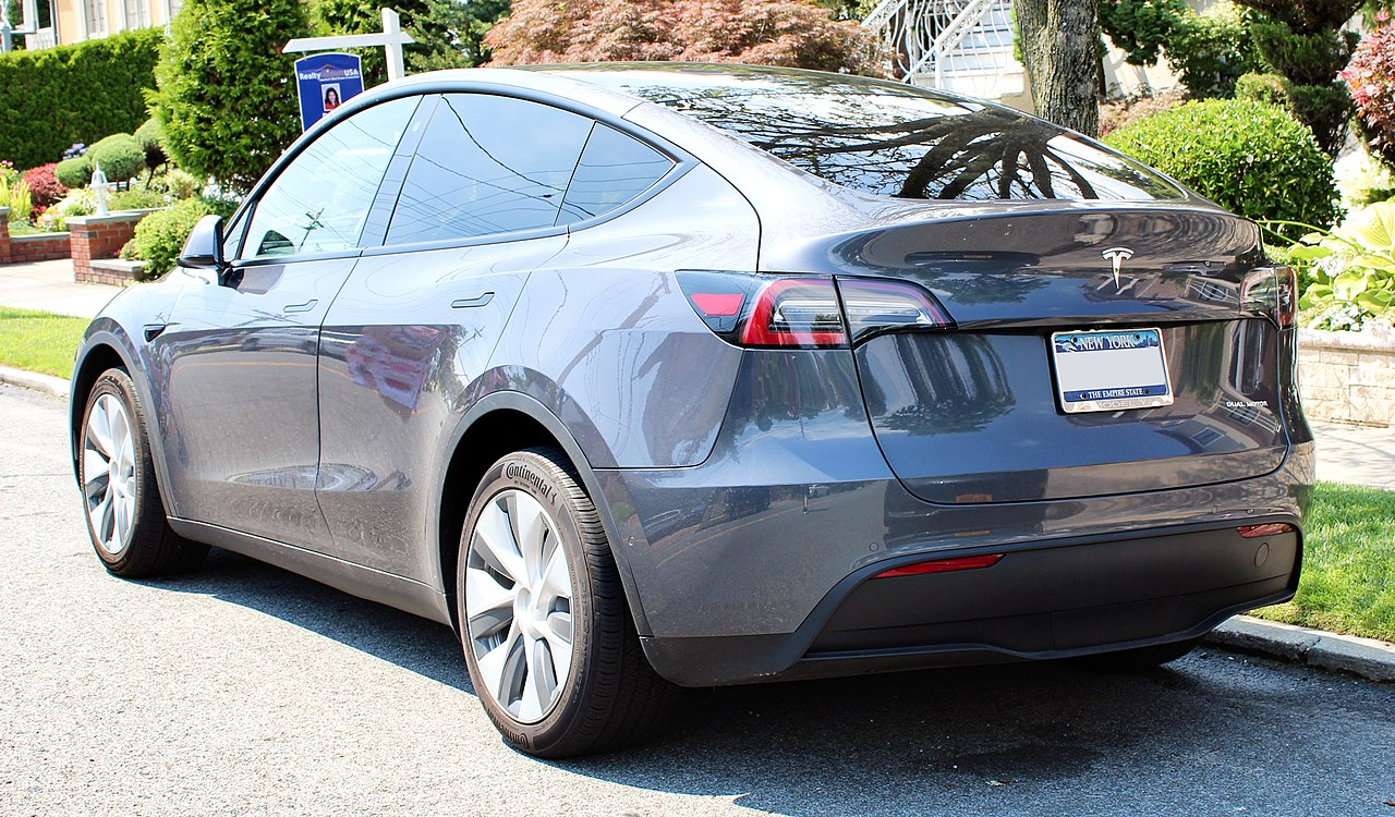 Photograph of the rear of a parked Tesla Model Y gray color.