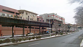 An elevated railroad track above a city street in winter, with two buildings. The smaller one, on the left, is pale yellow and narrow. The larger one at right, gray with a red stripe, is box-shaped and elevated over the tracks
