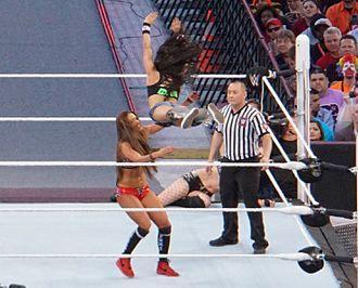 Professional wrestling aerial techniques - AJ Lee performing a diving crossbody on Nikki Bella at WWE WrestleMania 31.