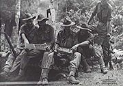 Military officers review maps in a jungle setting