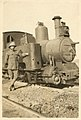 A British soldier leaning against a railway engine on the desert railway, 1917.jpg