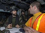 A French sailor, left, assigned to the visit, board, search and seizure (VBSS) team aboard the French Navy destroyer Jean de Vienne (D 643), interviews U.S. Navy Lt. j.g. Jeffrey Fasoli, the ordnance officer for 140101-N-PW661-042.jpg