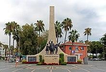 Высокий подметание каменный треугольник проецирует ввысь за статуи мужчины и двух детей из бронзы на меньшем подиуме.  Вокруг базы размещены несколько венков с логотипами.  Пальмы окружают сцену.