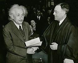 foto de blankhara viro sur maldekstraj (Albert Einstein) tremetantaj manoj kun viro en nigra robo.