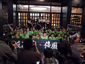 A group of protesters wearing green behind a black banner with Chinese writing in front of a building entrance surrounded by photographers