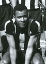 A young man sitting down, wearing a striped shirt. Behind him, three men wearing the same shirt and dark shorts are partially visible