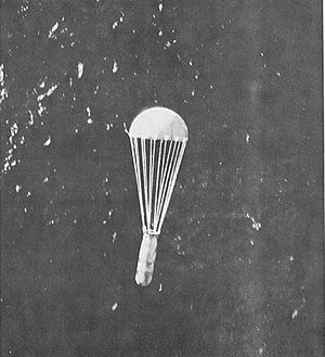 A parachute with a canister hanging below it dropping over the sea