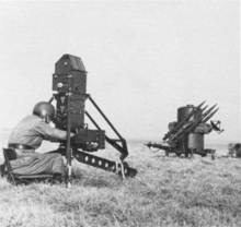 A two-wheeled trailer with four missiles on it. It has a radar dome, and a jerry can is attached to the trailer.