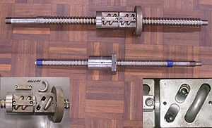 Ball screw - Photo showing two ball screws. Inset images are close-up photos of the ball assembly of the top screw. Left inset: recirculating tube removed showing retainer bracket, loose balls and tube. Right inset: closer view of the nut cavity.