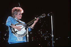 A blonde-haired woman wearing a sparkly blue jacket playing a banjo on stage
