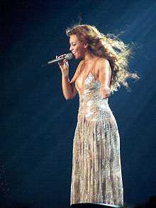 A black female singer with long, dark hair, singing on stage into a microphone in her right hand, wearing a silver, full-length dress.