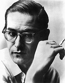 Tête d'un homme aux cheveux courts lissés et aux lunettes à monture d'écaille fumant une cigarette