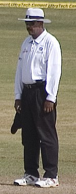 A dark skinned man standing, wearing white shirt, shoes and hat, along with a black pant and sunglasses. A cricket field and the boundary ropes can be seen in the background.