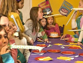 Party horn - Children blow party horns at a birthday party.
