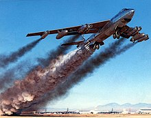 A shiny needle-nosed four-engine jet aircraft takes off. It is trailing an enormous amount of smoke.