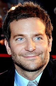 A photograph of Bradley Cooper, as he smiles away from the camera.