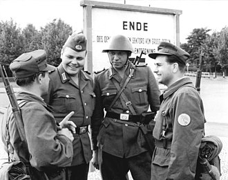 Combat Groups of the Working Class - Two members of a Combat Group chatting with NVA soldiers at the border of the Berlin-Sector in 1961