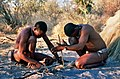 Khoisan men demonstrating how to start a fire by rubbing sticks together.