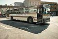 Buss fra ADS ventende på Arendal rutebilstasjon med reklamebanner fra Agderposten.jpg